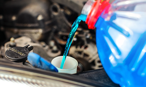 blue windshield wiper fluid being poured into car