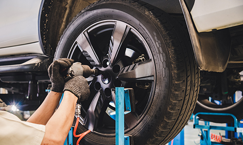 Man in tan shirt with black gloves unscrewing bolts from a tire